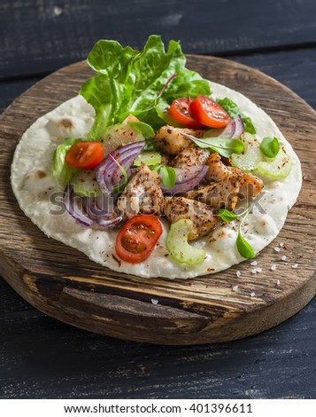 Delicious grilled chicken and fresh vegetables homemade tortilla on a rustic cutting board on a dark wooden background - stock photo
