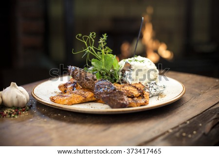 Delicious grilled chicken fillet and pork kebab with stuffed potato and vegetable garnish served on a wooden table, fireplace on background - stock photo