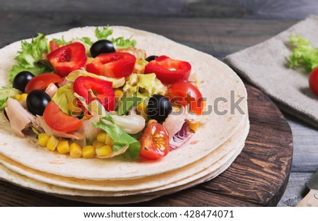 Delicious grilled chicken, fresh vegetables, homemade tortillas, black olives, stuffing, rustic cutting board on gray wooden background - stock photo