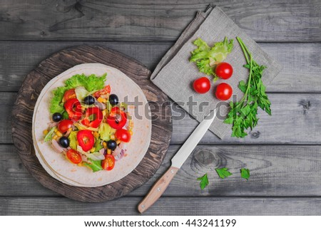 Delicious grilled chicken, fresh vegetables, homemade tortillas, stuffing, rustic cutting board on gray wooden background, top view - stock photo