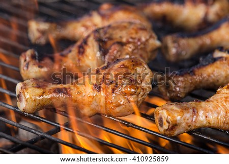 Delicious grilled chicken legs on a barbecue grill, close-up.