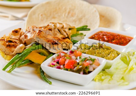 Delicious grilled chicken with a selection of sauces and vegetable accompaniments, spicy hot chili salsa and corn tortillas served on a plate