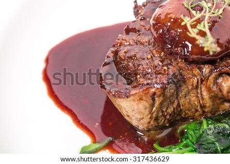 Delicious grilled fillet mignon steak with chard covered with red wine sauce. Macro. Selective focus on the top of steak. Photo can be used as a whole background. - stock photo