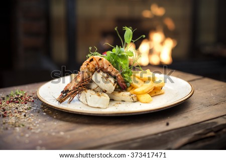 Delicious grilled king prawn with chicken fillet and homemade french fries served on a wooden table, fireplace on background - stock photo