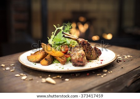 Delicious grilled pork ribs and potatoes with green garnish  served on a wooden table, fireplace on background - stock photo