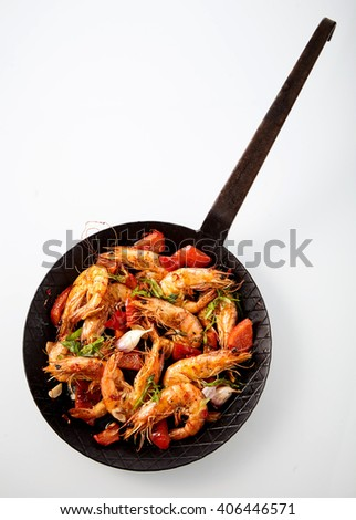 Delicious grilled prawn seafood appetizer with herbs, red bell pepper and garlic served in an old rustic pan, overhead view on white with copy space