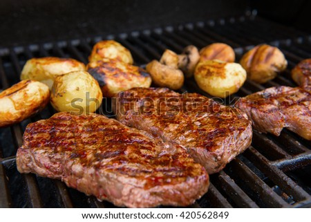 delicious grilled rump steak with mushrooms and potatoes on barbecue - stock photo
