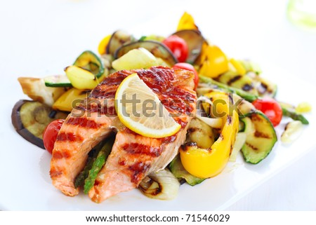 delicious grilled salmon steak with grilled vegetables on white plate - stock photo
