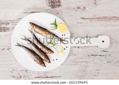 Delicious grilled sardines on wooden kitchen board on white wooden textured background. Culinary seafood eating.  - stock photo