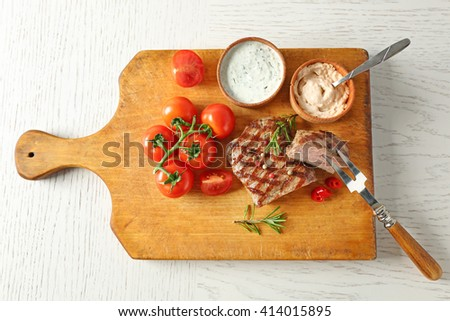 Delicious grilled steak on cutting board - stock photo