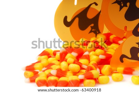 Delicious Halloween candy corn spilling out of a Halloween container. - stock photo