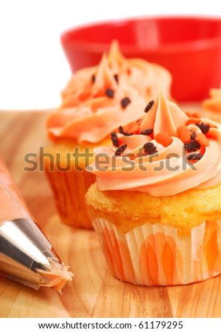 Delicious Halloween cupcakes being frosted and decorated - stock photo
