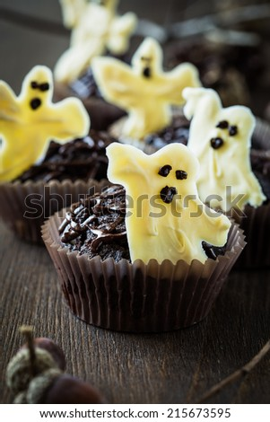 Delicious Halloween treat for dessert, chocolate muffins with  sweet white chocolate ghosts - stock photo