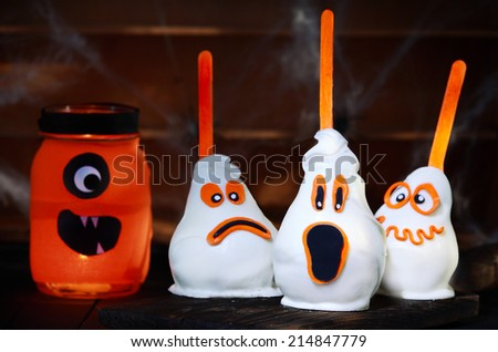 Delicious Halloween treat made of white chocolate coated pears next to a jar, all with funny scary faces