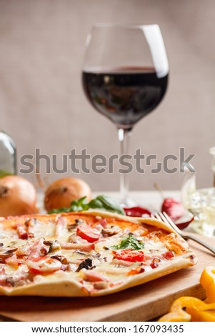 Delicious ham and tomato pizza on a thin crisp golden crust  - stock photo