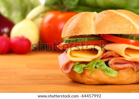 Delicious ham, cheese and salad sandwich, on a wooden board - stock photo