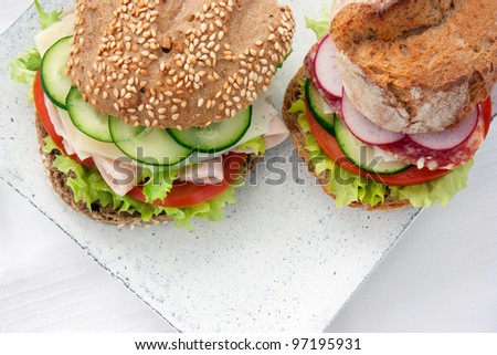 Delicious ham, cheese and salami sandwich with vegetables, lettuce, cherry tomatoes