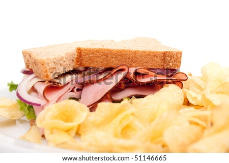 Delicious ham sandwich platter with whole wheat bread and potato chips
