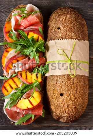 Delicious ham sandwich with grilled peaches and arugula on an wooden background. - stock photo