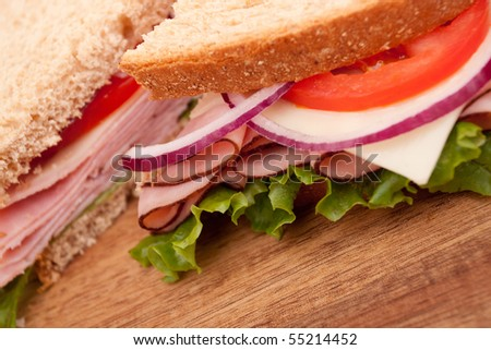 Delicious ham sandwich with whole wheat bread cut in half