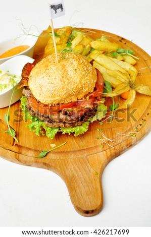Delicious hamburger and french fries isolated on white background. Hamburger, french fries, sauce on a wooden tablet.  - stock photo