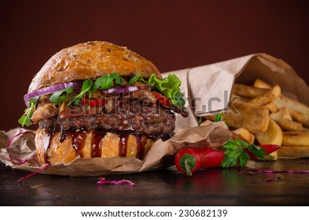 Delicious hamburger on dark background - stock photo