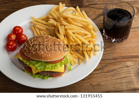 Delicious hamburger stacked high with a juicy beef patty, cheese, fresh lettuce, onion and tomato on a fresh bun with sesame seed standing on  wooden table - stock photo