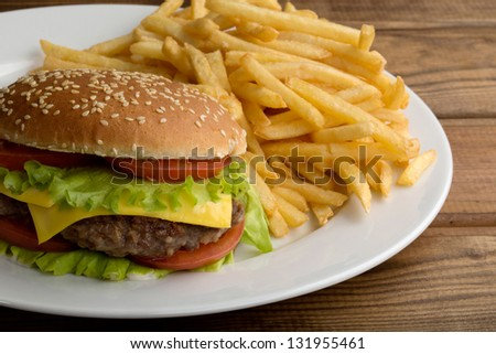 Delicious hamburger stacked high with a juicy beef patty, cheese, fresh lettuce, onion and tomato on a fresh bun with sesame seed standing on  wooden table