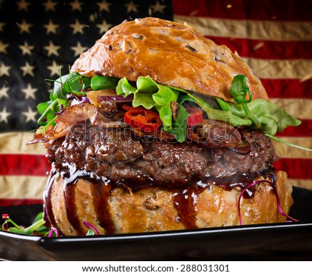 Delicious hamburger with fire flames and american flag on wooden background