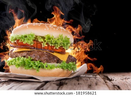 Delicious hamburger with fire flames on wooden background - stock photo