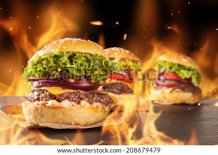 Delicious hamburgers with burning flames on background - stock photo