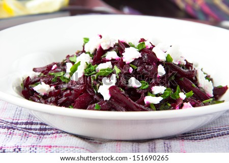 Delicious healthy beet salad with feta cheese, parsley and olive oil - stock photo