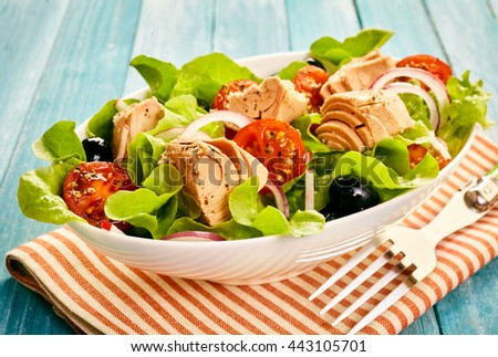 Delicious healthy fresh tuna salad served outdoors on a wooden table with leafy greens, tomato, olive and onion - stock photo