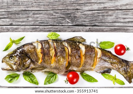 Delicious healthy grilled fish served on a platter with basil, lemon, cherry tomatoes for a tasty seafood dinner, top view - stock photo