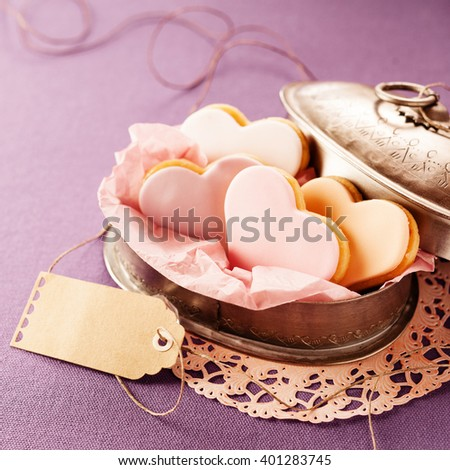 Delicious heart-shaped fondant cookies served in an open vintage tin with blank brown gift tag on a lilac background for Valentines Day, anniversary or wedding