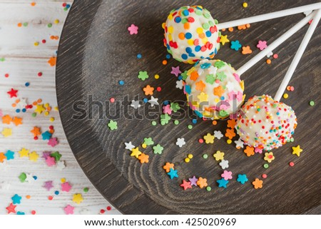 Delicious holiday colored cake pops in wooden plate. horizontal top view - stock photo