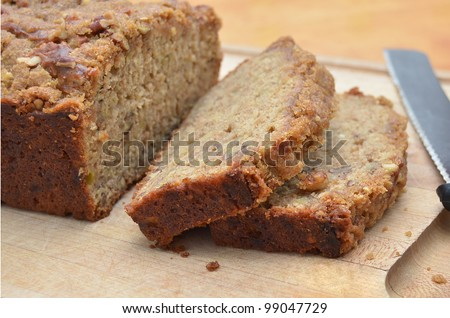 Delicious Home Baked Banana Bread, Sliced on a Cutting Board with a Knife, on a Wooden Kitchen Table - stock photo