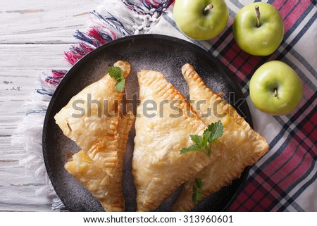 Delicious homemade apple pie turnover close-up on a plate. horizontal view from above