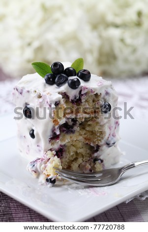 Delicious homemade blueberry cake with sour cream with a bite. Shallow DOF - stock photo