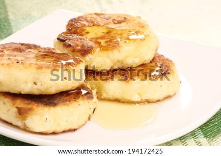 Delicious homemade cheese pancakes with honey closeup - stock photo