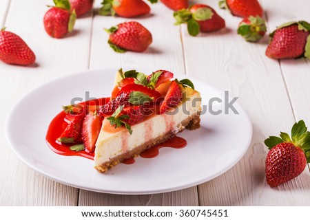 Delicious homemade cheesecake with strawberries  on  white wooden table. - stock photo