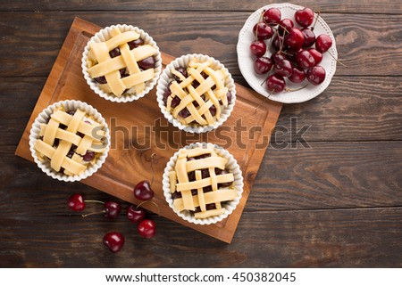 Delicious homemade cherry pies with fresh berries ready for baking, top view - stock photo