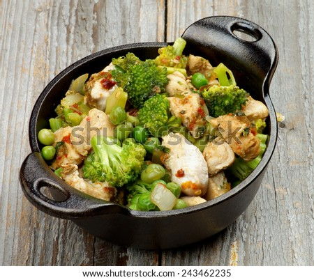 Delicious Homemade Chicken Stew with Green Pea, Broccoli and Bell Pepper in Black Saucepan isolated on Rustic Wooden background - stock photo
