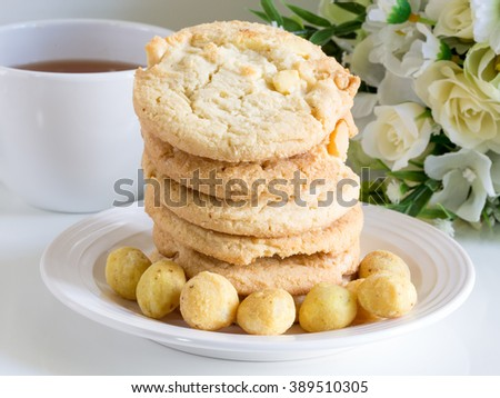 Delicious Homemade Cookies with Macadamia nuts and white chocolate,  cup of herbal tea with flowers - stock photo