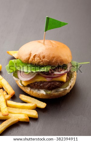 Delicious homemade hamburger with french fries on black wooden background - stock photo
