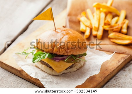 Delicious homemade hamburger with french fries on wooden background - stock photo