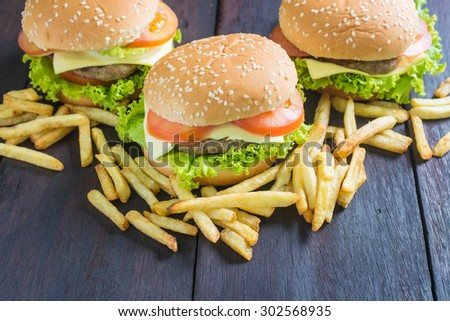 Delicious homemade hamburger with french fries on wooden desk.