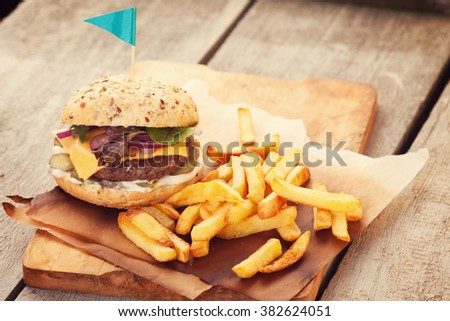 Delicious homemade hamburger with french fries on wooden vintage table