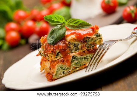 delicious homemade lasagne with ricotta cheese and spinach on wooden table - stock photo