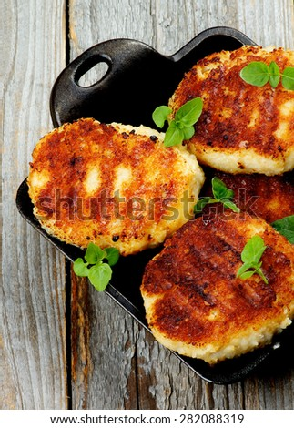 Delicious Homemade Meat Cutlets in Black Saucepan with Basil closeup on Rustic Wooden background. Top View - stock photo